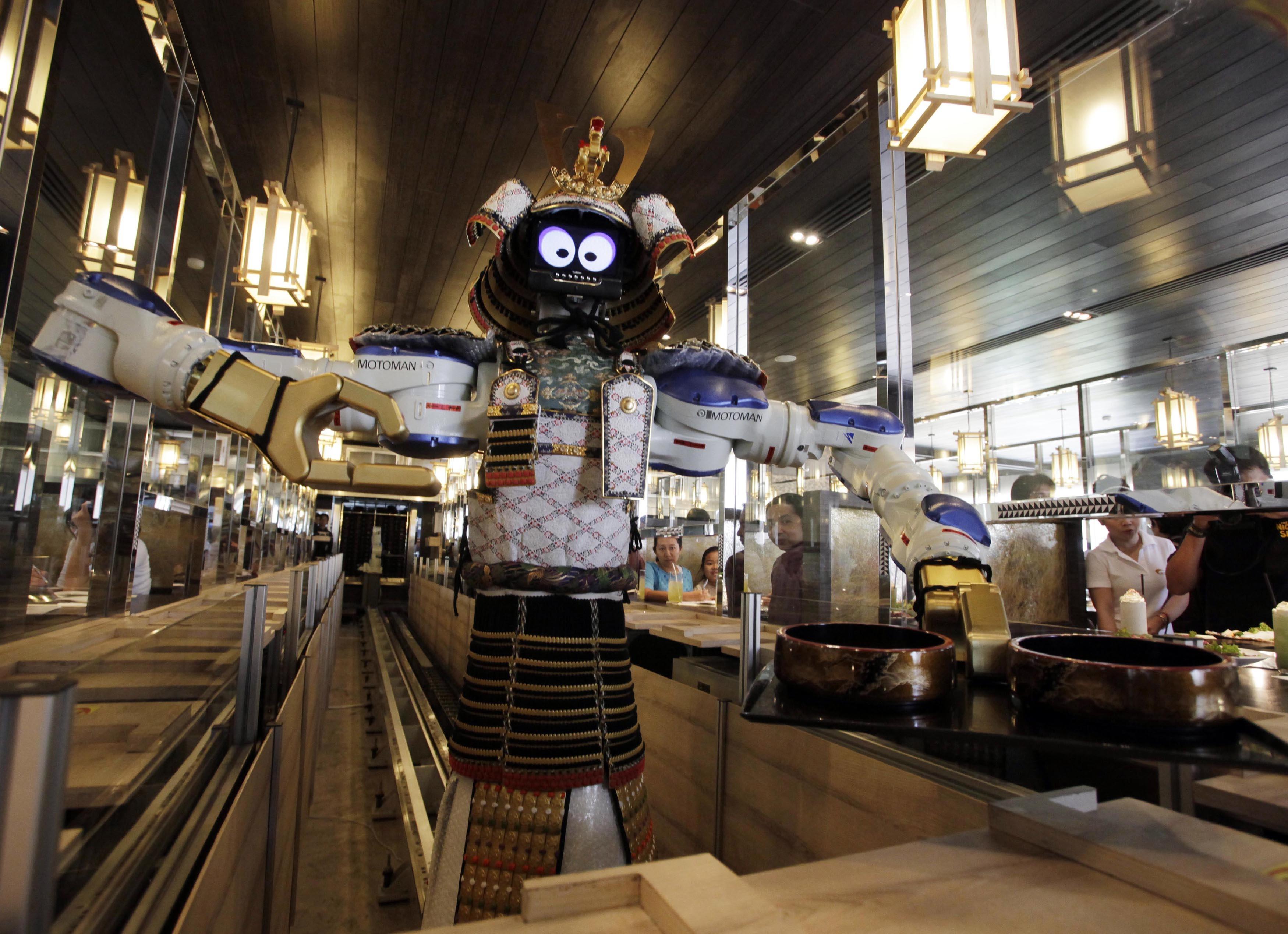 A robot waiter serves food to customers at Hajime Japanese restaurant in Bangkok