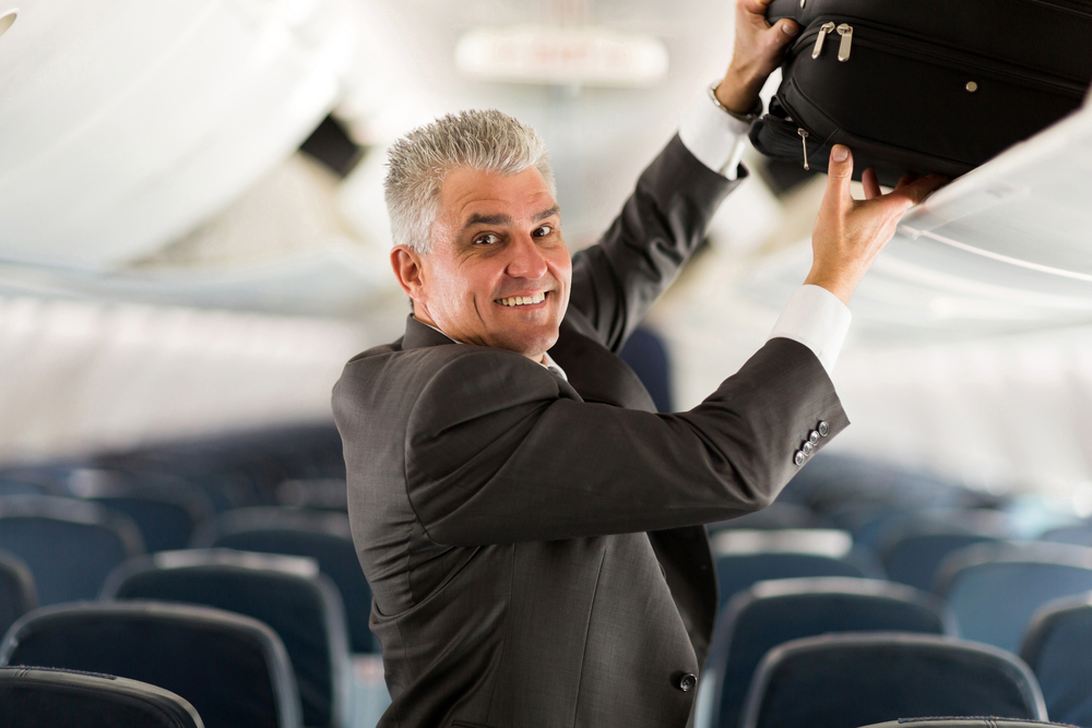 raveler putting luggage into overhead locker on airplane