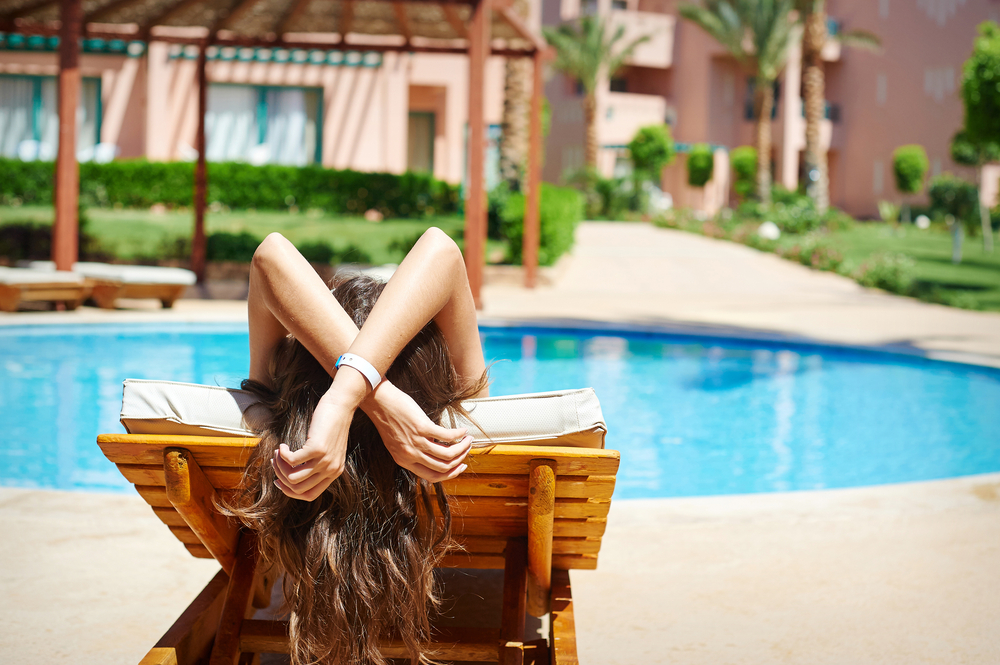 woman relaxing by pool on sunbed
